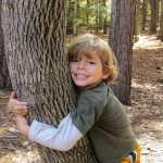 Five-year old Kyle Rockett gets cozy with a tree in the North Carolina woods.